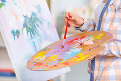 Young girl is busy oil-painting Stock Photography