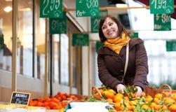 Young girl buying mandarins Stock Photo