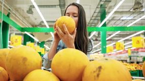 Young girl buys food for a vegan diet. Woman chooses fruit in supermarket. Healthy food, bright yellow vegetables in the. Young girl buys food for a vegan diet stock video footage