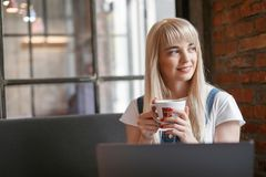 Young girl at cafe drinking coffee and using mobile phone. Online shopping. Beautiful woman using mobile phone and laptop while sitting at cafe. Young girl at royalty free stock photography