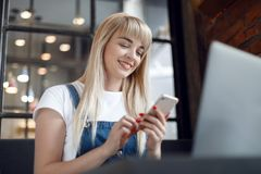 Young girl at cafe drinking coffee and using mobile phone. Online shopping. Beautiful woman using mobile phone and laptop while sitting at cafe. Young girl at stock photo