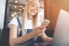 Young girl at cafe drinking coffee and using mobile phone. Online shopping. Beautiful woman using mobile phone and laptop while sitting at cafe. Young girl at stock photos