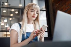 Young girl at cafe drinking coffee and using mobile phone. Online shopping. Beautiful woman using mobile phone and laptop while sitting at cafe. Young girl at stock photography