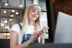 Young girl at cafe drinking coffee and using mobile phone. Online shopping. Beautiful woman using mobile phone and laptop while sitting at cafe. Young girl at royalty free stock photos