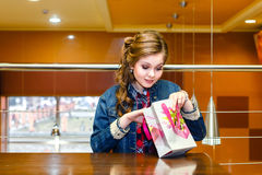 Young girl in a cafe looking in gift bag Stock Image