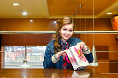 Young girl in a cafe opens a gift bag and smiling Royalty Free Stock Image