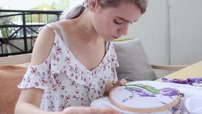 Young girl at cafe sewing with needle. needlework, embroidery, hobby, handicraft stock footage