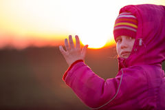 Young girl calling her hand at sunset Stock Images
