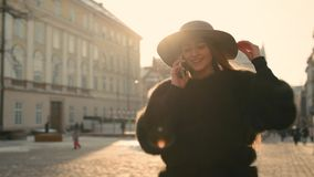 Young girl calling somebody on the phone, talking and smiling happily. Attractive young girl calling somebody on the phone, then gladly talking and smiling stock footage