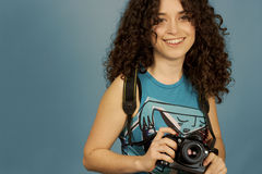 Young girl and a camera. Young and Pretty Student over blue background Stock Image