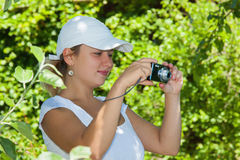 Young girl with a camera. Young girl photographed digital compact camera Stock Image