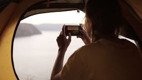 Young girl camping alone. Girl is taking a photo from her smartphone. Beautiful view from the outside of the tent - sea. Or lake on blurred background. Footage stock video footage