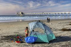 Young Girl Camping on La Jolla Shores Beach north of San Diego California. Young girl playing with toys in the sand near camping tent on La Jolla Shores Beach Stock Photography