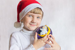 Young girl in cap Santa Claus on a white background holds Christmas ball. Portrait of a child. Royalty Free Stock Photography