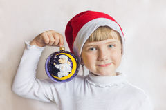 Young girl in cap Santa Claus on a white background holds Christmas ball. Portrait of a child. Royalty Free Stock Image