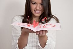Young girl with card with pop up hearts Royalty Free Stock Photos