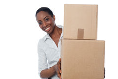 Young girl with cardboard boxes in hand. Smiling woman holding cardboard boxes for shipment Stock Image