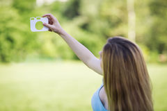 Young girl with a cardboard symbol of camera.  Royalty Free Stock Photo