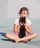 Young girl caress with kitten. Girl craddle kitten in arms Stock Image