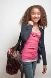 Young girl carrying bag full of books Royalty Free Stock Image