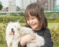 Young girl carrying dog Stock Photography