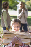 Young girl carrying firewood Stock Images