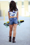 Young girl carrying skate board Stock Photos