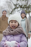 Young girl carrying snow balls in front of parents in park in winter Royalty Free Stock Images