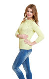 Young girl casual dressed blue jeans and a green sweater posing in studio on white background Royalty Free Stock Photo