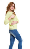 Young girl casual dressed jeans and a green sweater posing in studio show best gesture on white background Royalty Free Stock Photo