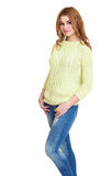 Young girl casual dressed jeans and a green sweater posing in studio on white background Royalty Free Stock Photo