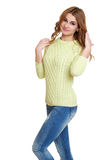 Young girl casual dressed jeans and a green sweater posing in studio on white background Royalty Free Stock Images