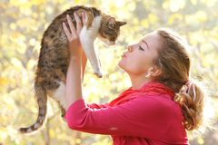 Young girl with cat on natural background Royalty Free Stock Photos