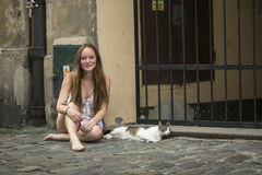 Young  girl with a cat sitting on a stone pavement. Stock Images