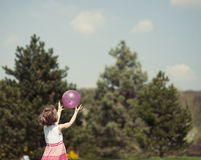 Young girl catching purple ball in park Royalty Free Stock Images