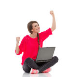 Young girl celebrates success with laptop. Excited young woman is sitting on the floor with legs crossed, holding laptop and smiling with arms raised. Full Royalty Free Stock Image