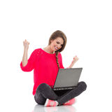 Young girl celebrates success with laptop. Excited young woman is sitting on the floor with legs crossed, holding laptop and smiling with arms raised. Full Stock Photography
