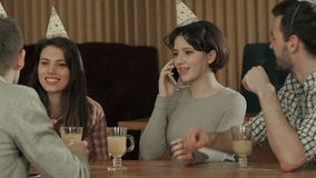 Young girl celebrating birthday in cafe, talking on cell phone. Professional shot in 4K resolution. 088. You can use it e.g. in your commercial video, business stock footage