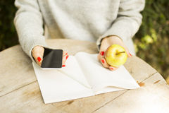 Young girl with cell phone, diary and green apple Royalty Free Stock Image