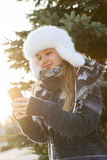 Young girl with cell phone in winter Royalty Free Stock Photos