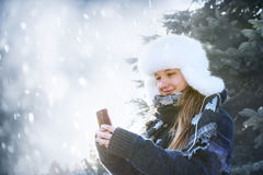 Young girl with cell phone in winter Royalty Free Stock Photo