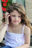 Young girl on a cellphone. Young little girl talking on the cell phone, with long blond hair, shallow depth of field Royalty Free Stock Photos