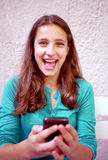 Young girl and cellphone. Young girl types out a text message Royalty Free Stock Images
