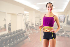 Young girl with centimeter tape at gym club Royalty Free Stock Photos