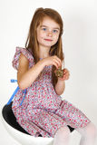 Young girl on the chair. Young smiling girl sitting on a chair. smelling perfume Royalty Free Stock Photography