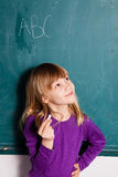 Young girl and chalkboard with letters Stock Images