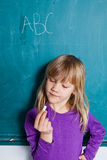 Young girl and chalkboard with letters Stock Photo