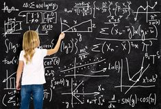 Smart Girl, Math, Arithmetic, Education, Learning. A young girl is at a chalkboard writing complex math equations and arithmetic formulas. A smart kid learns in Stock Images