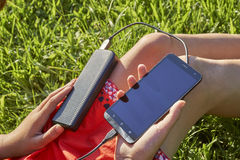 Young girl charging her smart phone with power bank sitting on green grass outdoors. Girl holding powerbank connected with mobile phone sitting on green grass Stock Photo