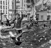 Young Girl Chasing Pigeons Stock Photo